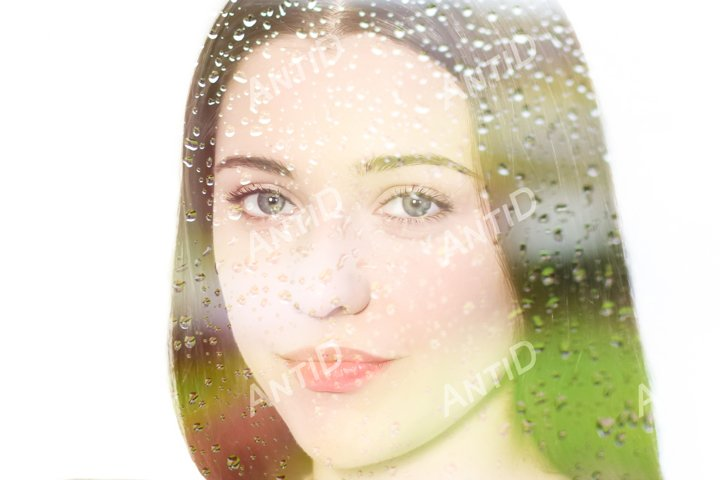 Portrait of a girl on a white background through raindrops.