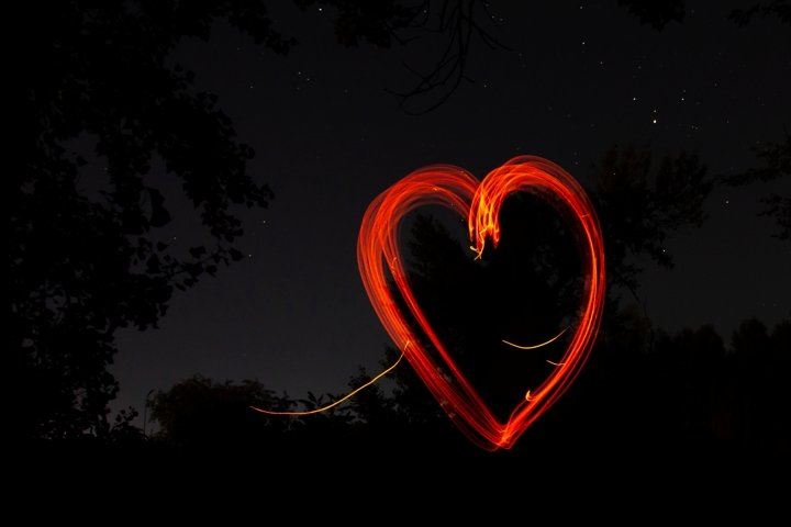 Red heart drawn by fire on black night background
