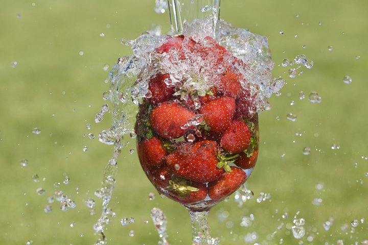 flow of water directed into glass with red strawberries