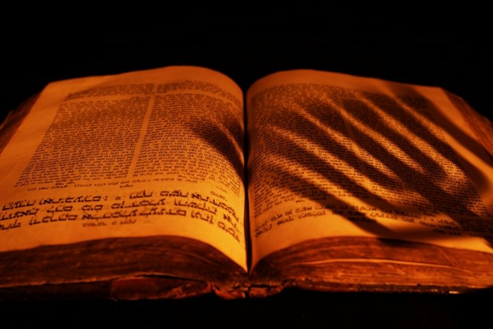 Old Hebrew Bible in light of candle on dark background