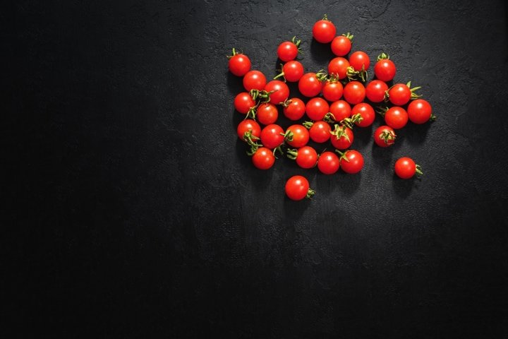 Ripe cherry tomatoes on black background