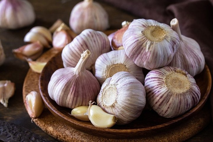 Garlic Cloves and Bulb on rustic wooden table.