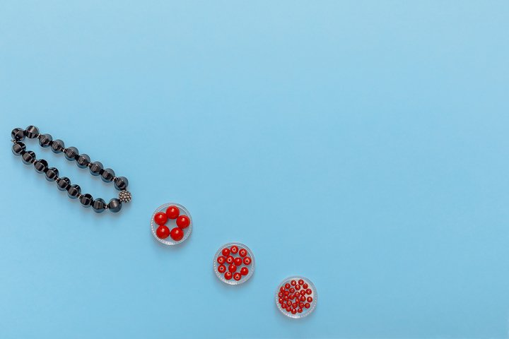 Flat lay of black pliers, red coral beads