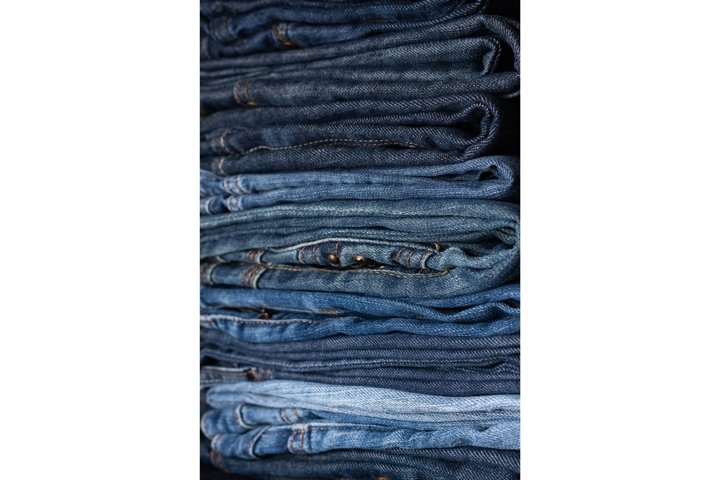 Stack of blue jeans of different shades. Jeans background