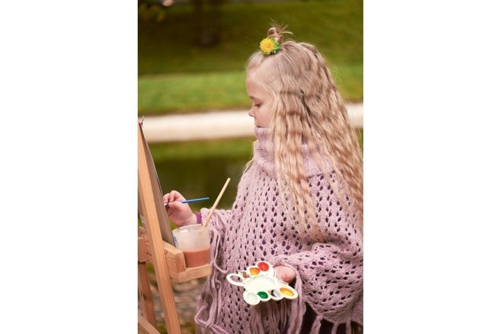 ittle girl painting a picture in the park