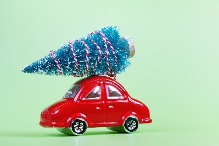 Glass red toy car with christmas tree on green