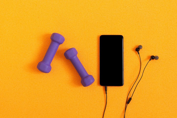 Dumbbells, smartphone and headphones on background