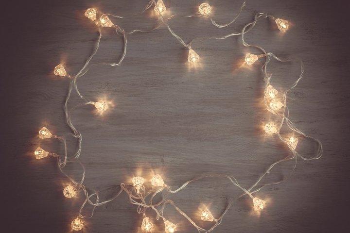 Fairy lights frame on dark wooden christmas background
