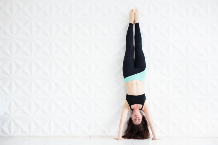 Young brunette woman doing a handstand