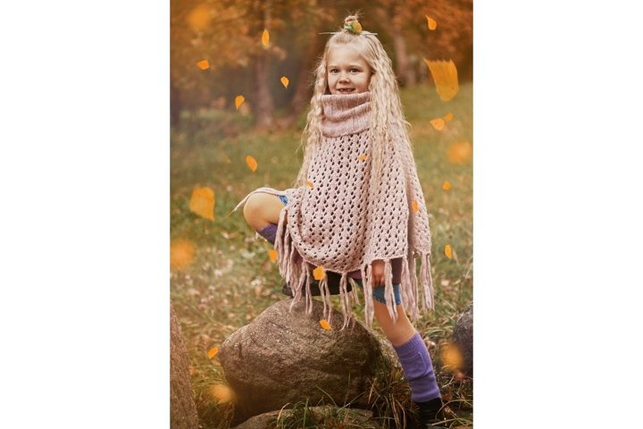 autumn portrait of a cute little girl wrapped in a big scarf