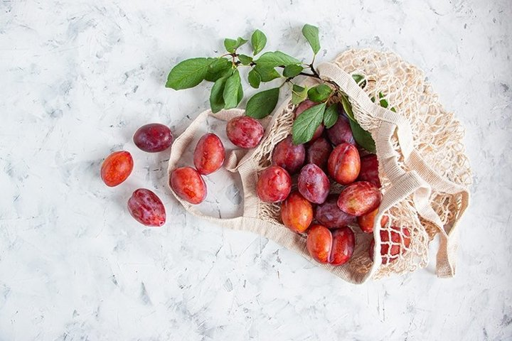 Ripe plum in a cotton mesh bag.