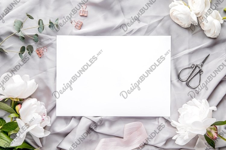 Flat lay with white paper sheet and fresh white peonies