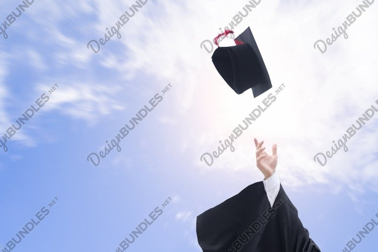 Graduates throwing graduation hats in the air. example image 1