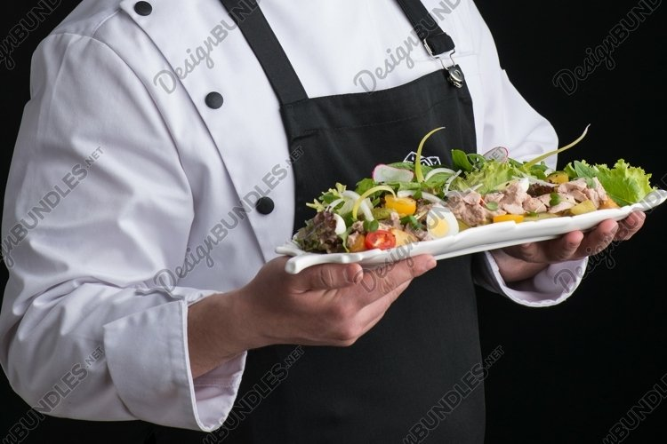Chef in uniform serves a dish in a plate example image 1