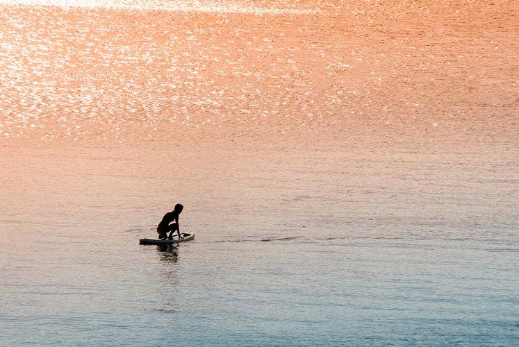 Kneeling on paddle surfer girl
