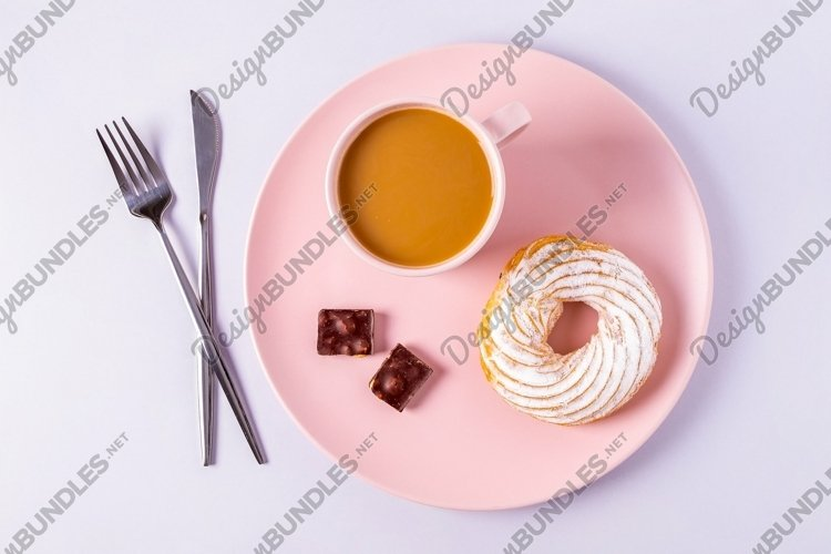 Cake on a pink plate, cutlery and cups with cocoa or coffee example image 1