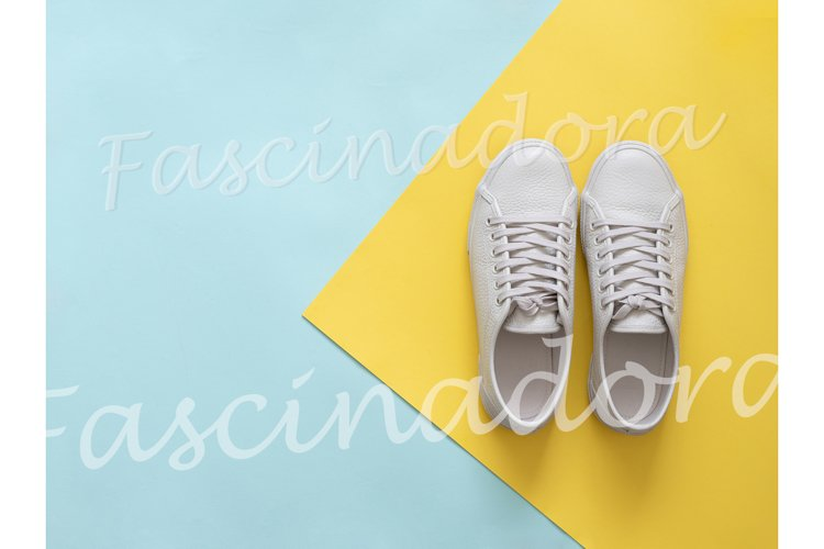 White sneakers on blue and yellow, copy space, top view example image 1