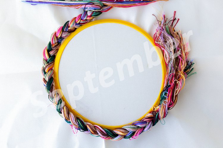 Multucolored threads made into a braid around canvas hoop example image 1