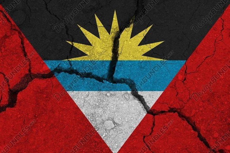 Antigua and Barbuda flag on the cracked earth.