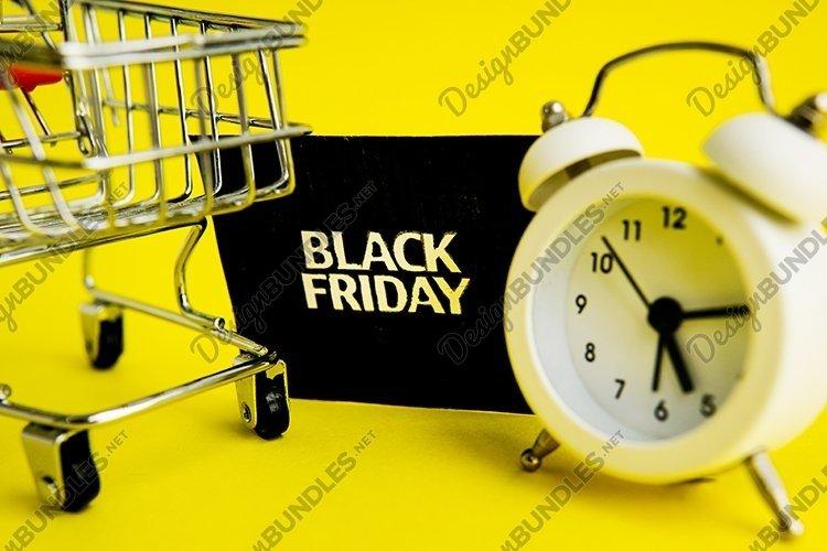 White alarm clock, a shopping cart, black Friday example image 1