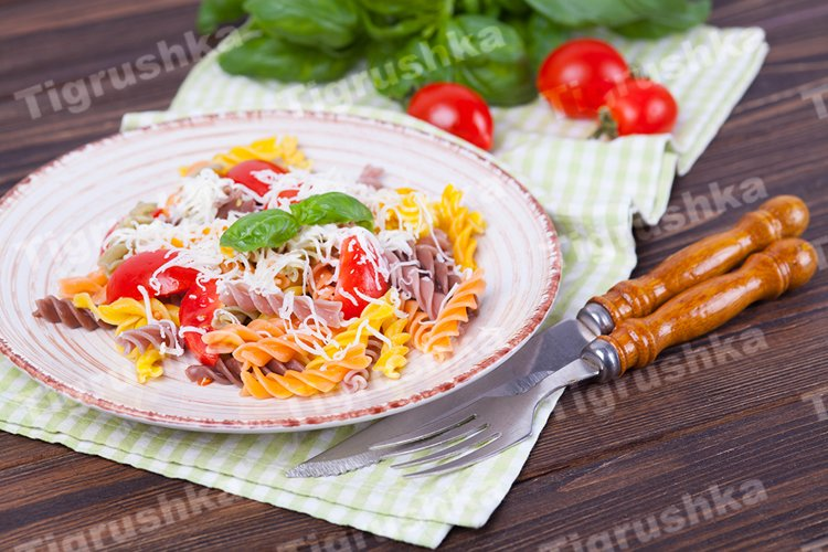 colorful pasta fusilli with tomato, basil and cheese