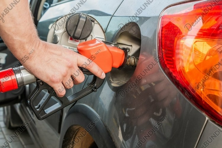 A man refueling his gray car