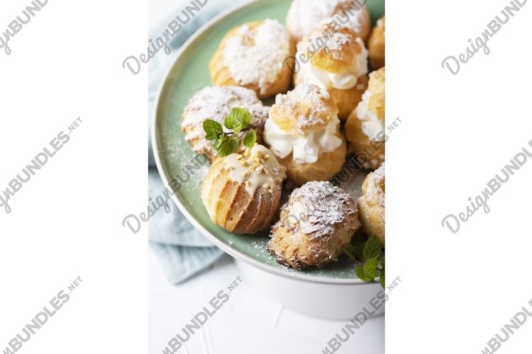 Mix of different profiteroles with cream, selective focus example image 1