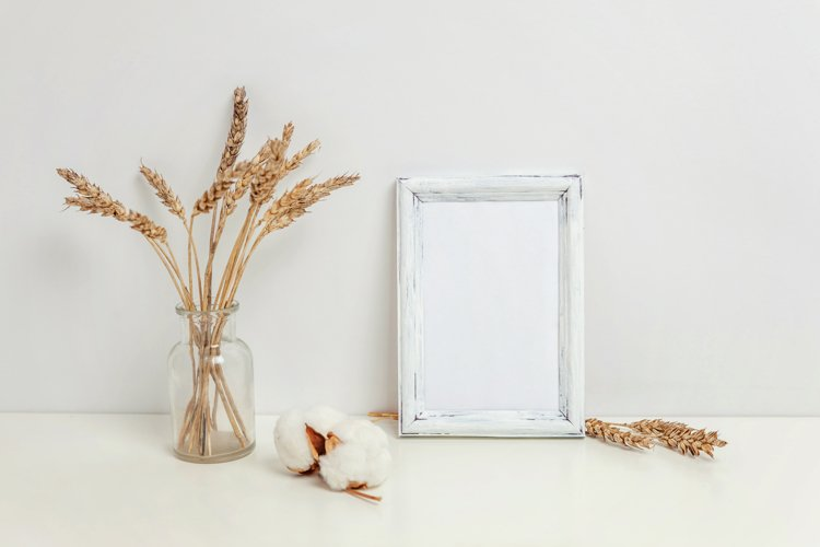 Vertical frame mockup with rye bouquet in vase, white wall example image 1