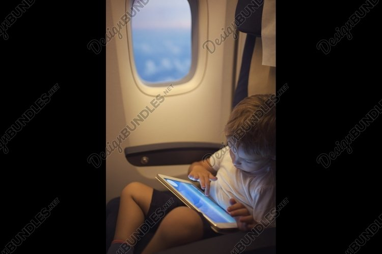 Boy spending time with tablet PC during flight example image 1