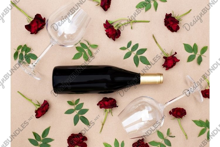 Empty wineglasses and a bottle with fresh red roses