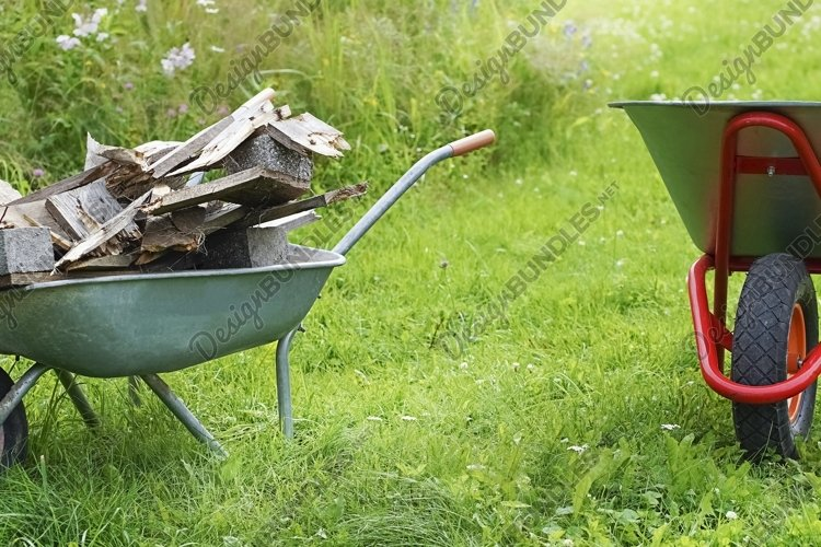 Two wheelbarrows with firewood on green lawn background example image 1