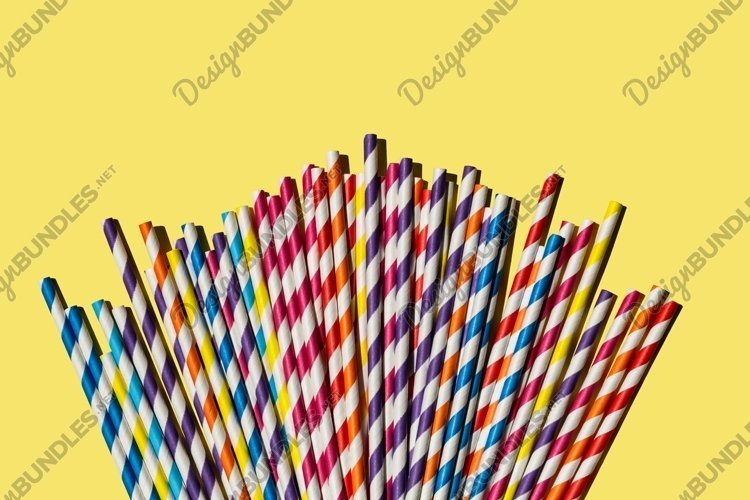Multi-colored paper tubes for party on yellow background. example image 1
