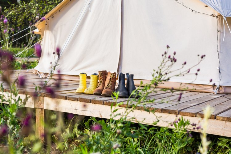 Close-up of a canvas bell tent with shoes on a wooden base