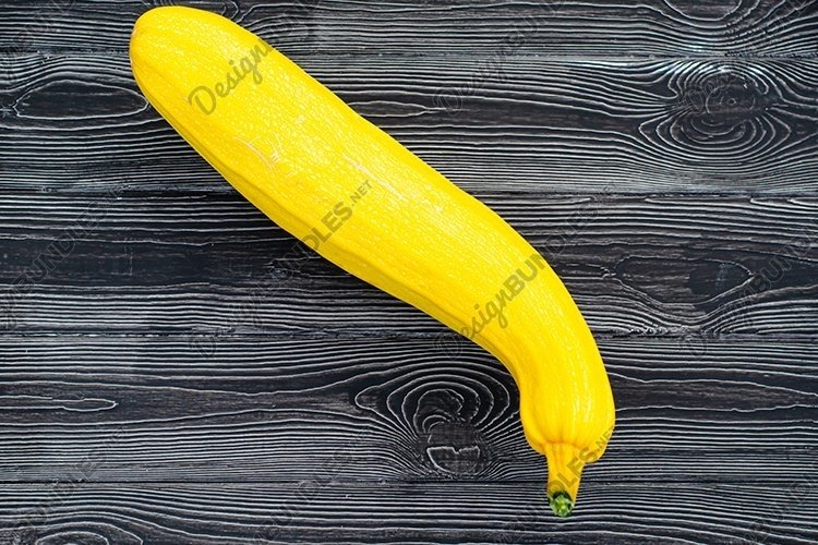 Yellow zucchini on a dark wooden background. example image 1