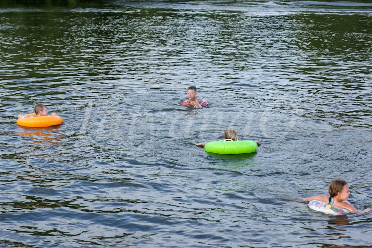 children swim with the inflatable circles in the river example image 1