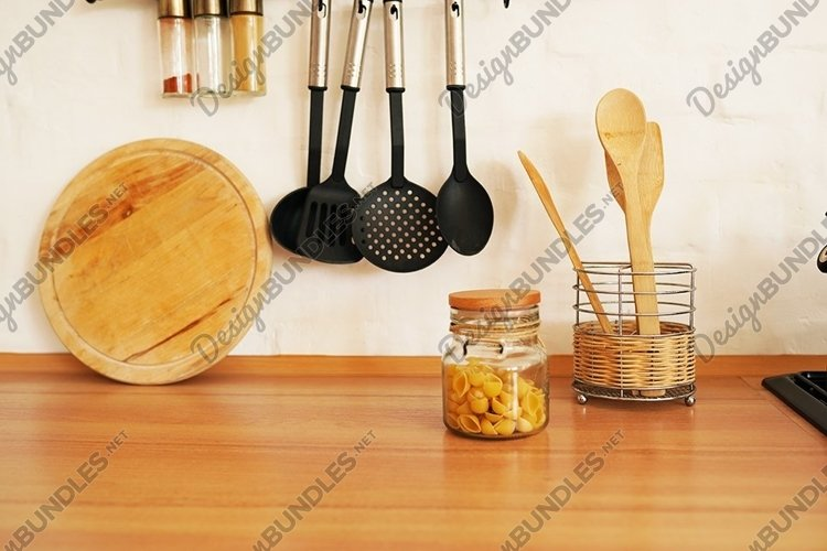 Kitchenware with wooden spoons in vase on wooden table example image 1