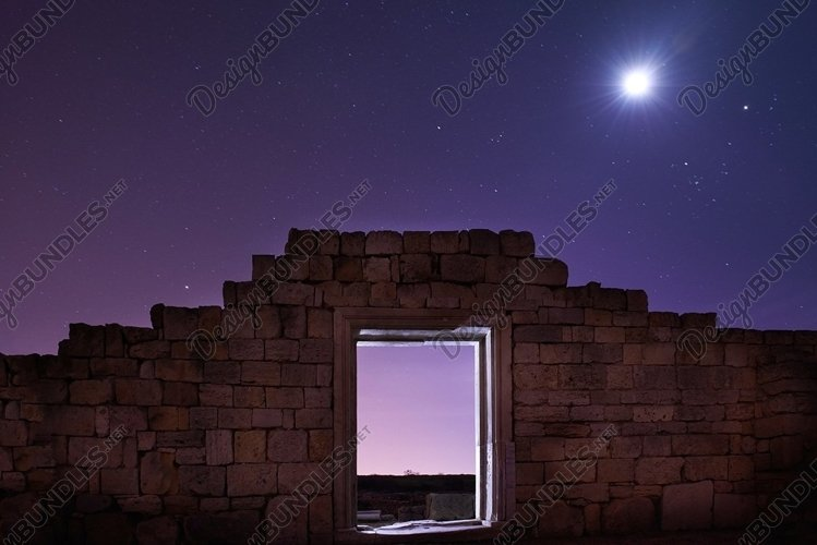 Ruins of ancient city under blue night sky with moon example image 1