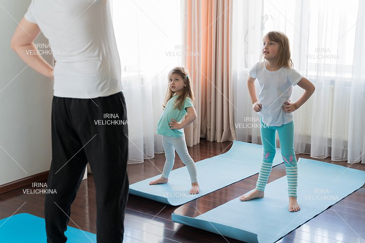 Home fitness yoga workout.Dad teaches little girls exercises