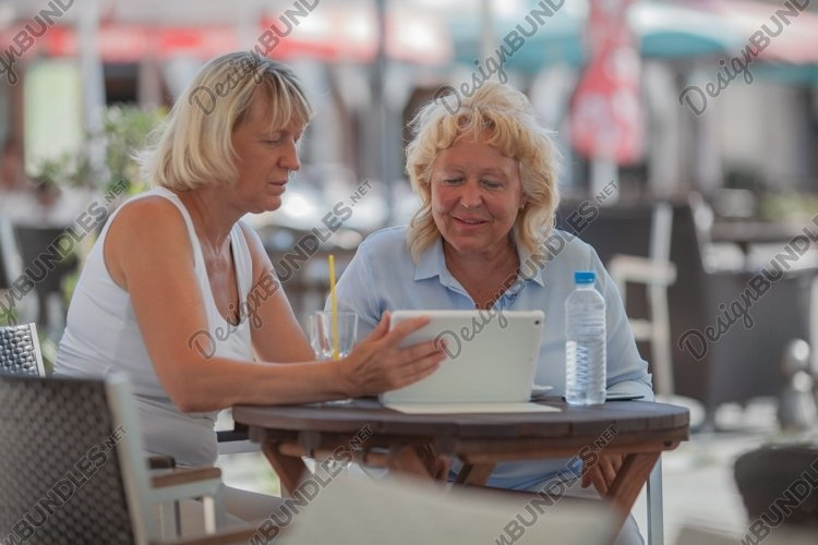 Senior women relaxing in cafe and using digital tablet example image 1