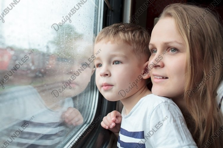 Mother and son looking through a train window example image 1