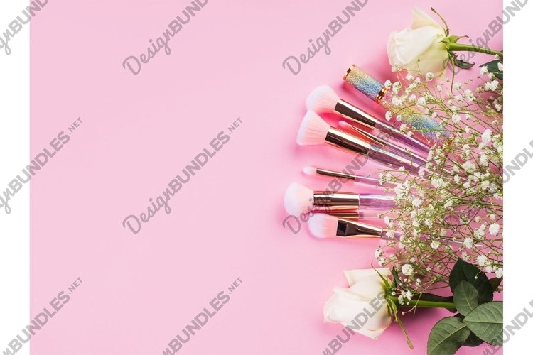 Shiny make up products and accessories on pink background
