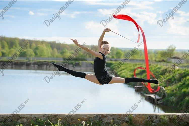 Gymnast girl doing leg-split in a jump with ribbon example image 1