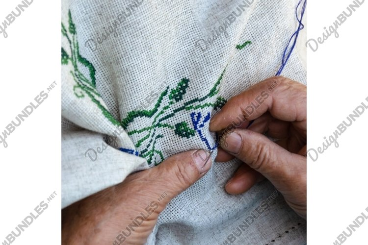 Elderly woman's hands embroidering cross stitch pattern example image 1