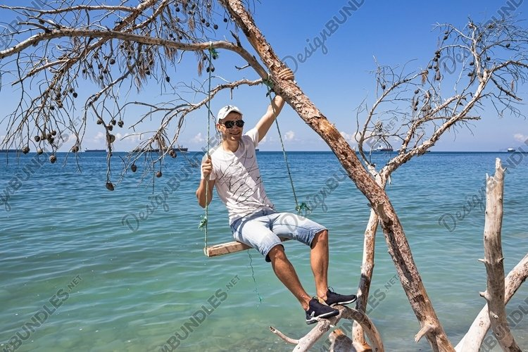 A guy is sitting on a swing made of a fallen tree. 3pcs example image 1