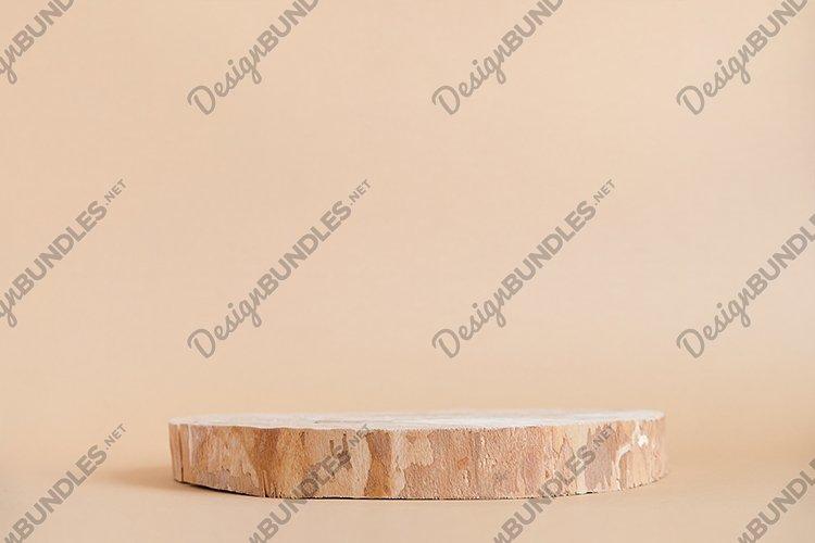 Round wooden saw cut cylinder shape on beige background