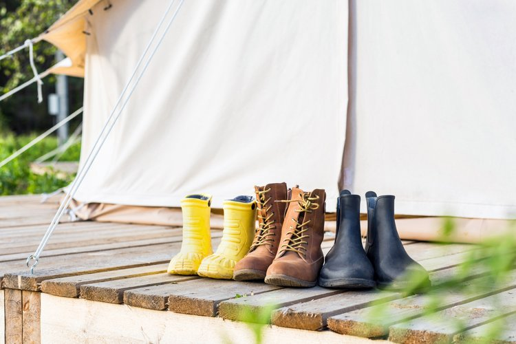 Three pair of shoes on wooden terrace behind a canvas tent