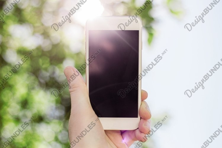 mobile phone in hand against the background of the sun example image 1