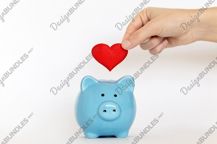 Hand putting red heart into piggy-bank