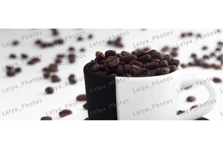 Coffee beans in a black and white cup of espresso