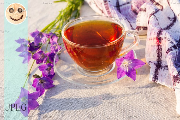 Cup of tea on checkered napkin and bluebell flowers
